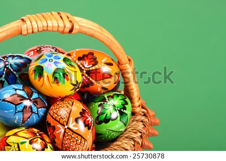 Easter Eggs  in wicker basket on green background