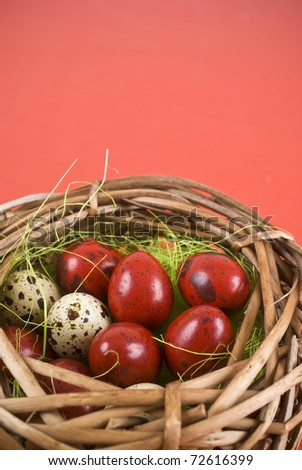 Easter eggs in wicker basket on red background