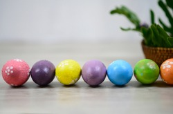 Easter eggs on Easter day background with colorful Eastereggs lined up, rattan basket decoration on white wooden table background. Easter holiday concept. Copy paste for your text or design.