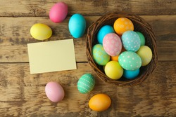 Easter eggs on wooden background with blank card