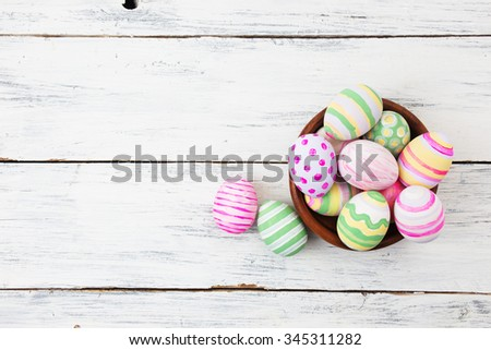 Easter eggs painted in pastel colors on white wooden background. Easter concept