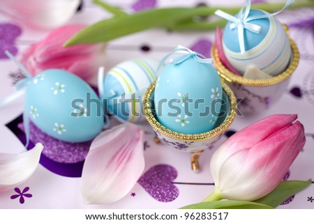 Easter eggs, pink tulips and petals