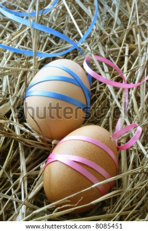 Easter eggs tied with satin ribbon, on a bed of straw.  Symbols of rebirth.