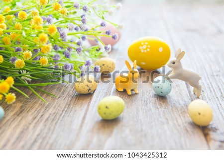 Easter eggs with flowers and small bunny toys on wooden board, easter holiday concept. #1043425312