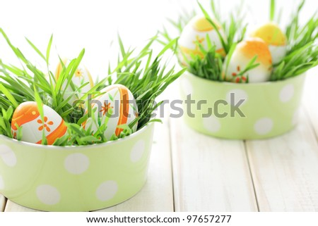 Easter eggs with fresh grass on table.