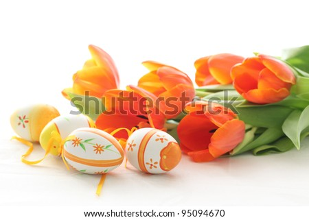 Easter eggs with orange tulips isolated on white background
