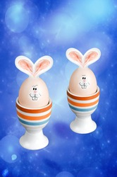 Easter eggs with rabbit ears and muzzles on a blue fractal background. The concept of Easter