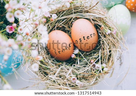 Easter eggs with rubber stamp 'Frohe Ostern' greeting text, Happy Easter in german, in a hay and flowers on a white wooden background Stock foto ©