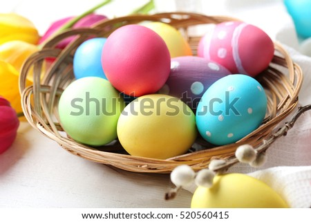 Easter eggs with tulips on a white wooden table