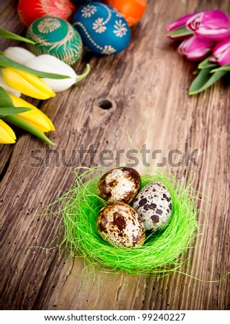 Easter eggs with tulips on wooden background