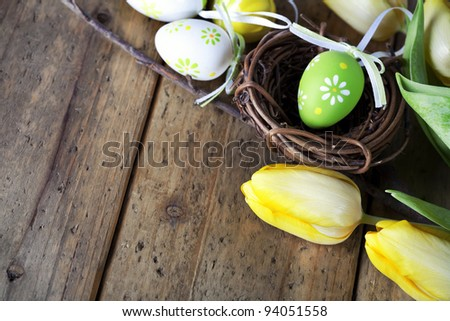 easter eggs with yellow tulip flowers  isolated on wooden board