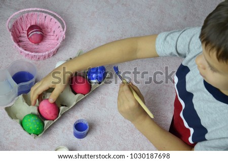 easter, family, holiday and child concept - close up of little boy coloring eggs for easter. #1030187698