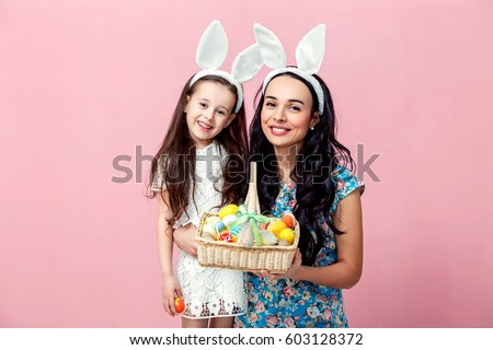 easter, family, holiday and child concept - close up portrait of little girl and mother coloring eggs for easter.