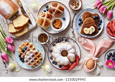 Easter festive dessert table with hot cross buns, cakes, waffles and pancakes. Overhead view #1310029945
