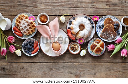 Easter festive dessert table with hot cross buns, cakes, waffles and pancakes. Overhead view #1310029978