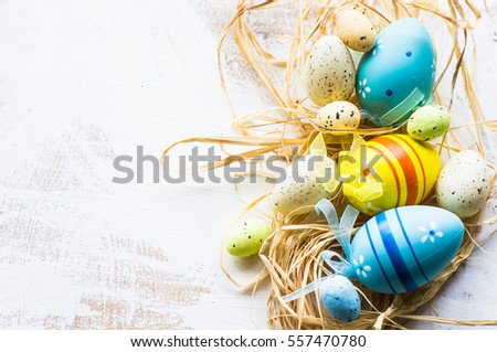 Easter festive frame with eggs, tulips and easter bunny on white rustic wooden table with copyspace #557470780