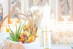 Easter food basket for blessing in church, catholic eastern european custom with eggs, spring onion, ham and bread, artistic edit