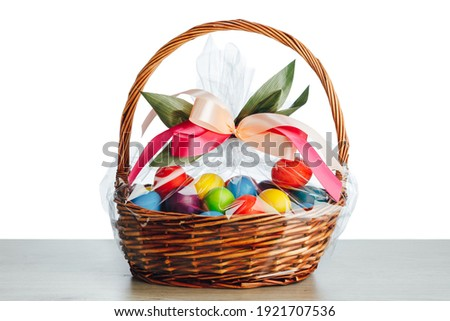 Easter gift basket with multicolor eggs, white background Stockfoto ©