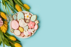 Easter gingerbread with icing on plate, seasonal flowers on blue, festive Easter background web banner, copy space. Easter card with traditional treats. Sweet Easter concept, greeting card