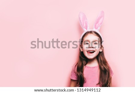 Easter girl portrait. Cute little girl with bunny ears on pink background. Easter child portrait, funny emotions, surprise. Copyspace for text.