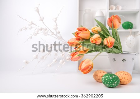 Easter greeting card design with bunch of tulips and painted eggs on abstract white background