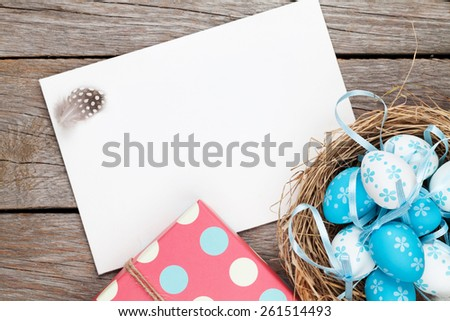 Easter greeting card with blue and white eggs and gift box over wood Top view with copy space