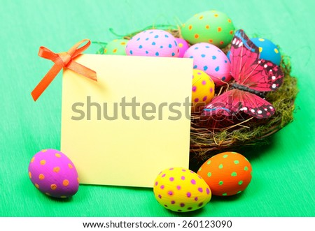 Easter greeting card with eggs in nest on green background