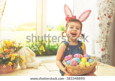 Easter. happy child girl with bunny ears and colorful eggs sitting at the window of a house in flowers #383348890