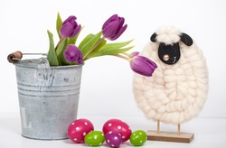 Easter holiday background of colorful Easter eggs, pink tulips in bucket and cute little sheep