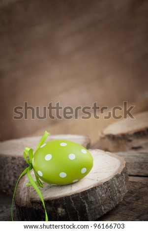 Easter holiday background with easter egg in natural wood setting