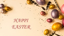 Easter holiday. Beautiful, multi-colored, mother-of-pearl eggs lie on a uniform beige background. Feathers all around.