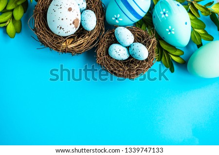 Easter holiday card concept with blue colored eggs and boxwood on pastel blue background with copy space
