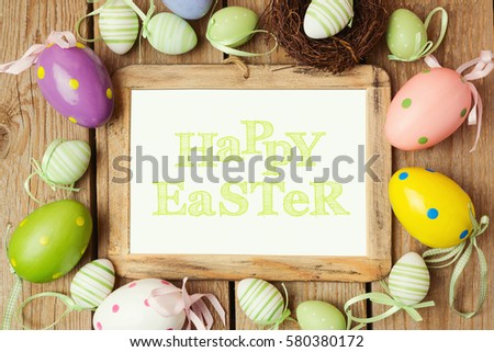 Easter holiday concept with eggs decorations and photo frame on wooden background. Top view from above
