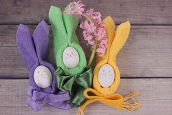 Easter holiday table setting with multicolored eggs on barn boards.Pink hyacinth, rabbits from eggs, yellow, green and purple napkins with bows on wooden background. Top view with copy space for text.