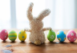 easter, holidays, tradition and object concept - close up of colored easter eggs and bunny