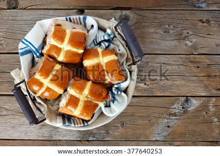 Easter Hot Cross Buns in a basket, downward view on a rustic wood background