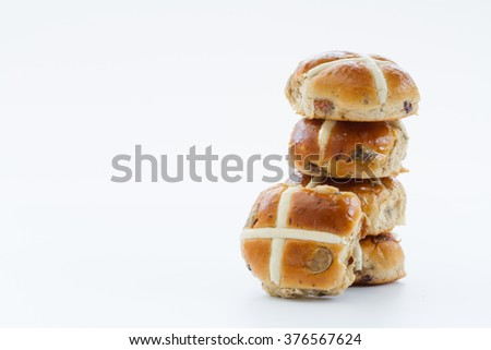 Easter Hot Cross Buns stacked up and isolated on a white background.
