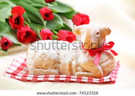 Easter lamb cake and red tulips on white background