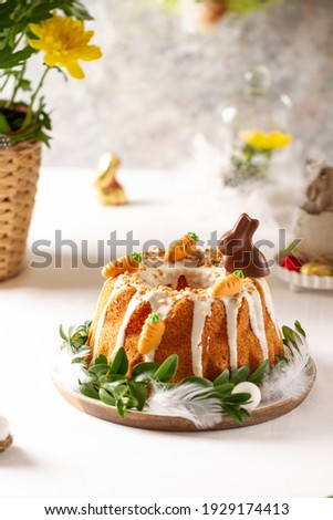 Easter lemon cake with icing and easter decoration. Easter gugelhupf cake with marzipan carrots and chocolate easter bunny