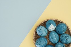 Easter pastel background. Easter trending blue eggs in a wicker basket on a two-tone blue and yellow background. The concept of Easter, holiday, postcards. Copy space, top view, flat lay