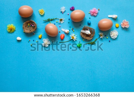 Easter pattern of Eggs with flowers, nests and candies on the blue background. Easter concept. Healthy feeding concept.