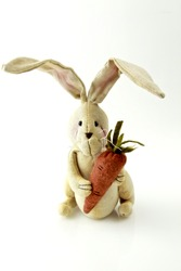 easter rabbit toy with carrot on a white background