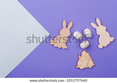 Easter rabbits from plywood. Easter bunnies wooden cutouts and styrofoam eggs on purple background. Easter spring concept. #1053797660