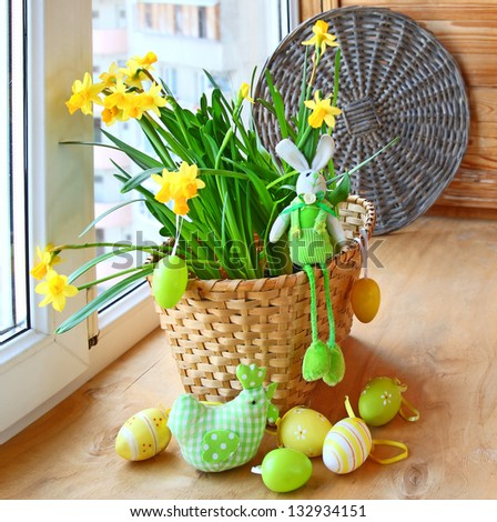 Easter still life with a happy rabbit, chicken and easter eggs in the yellow daffodils in a basket