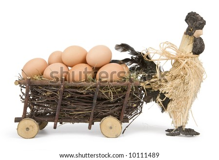 Easter straw cock with old-fashioned wooden cart full of eggs on white background