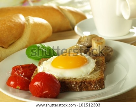 Easter sunny side up egg on a slice of bread with tomatoes with a French loaf.
