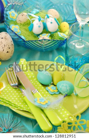 easter table decoration with eggs on the plate in pistachio and turquoise colors