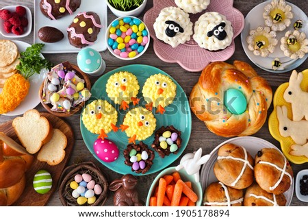 Easter table scene with an assortment of breads, desserts and treats. Top view over a wood background. Spring holiday food concept.
