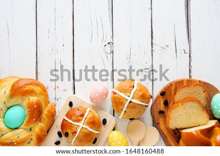 Easter table scene with an assortment of fresh breads. Overhead view bottom border over a white wood background. Spring holiday baking concept.