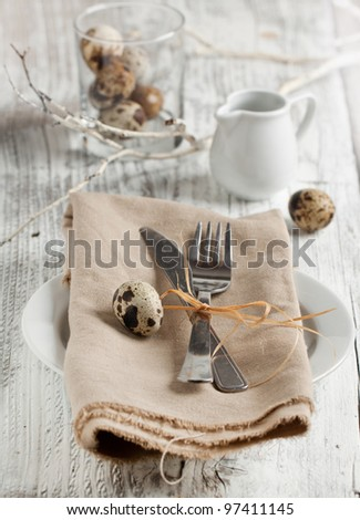 Easter table setting chicken and quail eggs on white wooden table